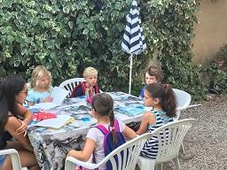 En grupp med barn 6 - 8 år i fin miljö med lärare Laura på f.m. i trädgård