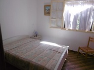A bedroom with a double bed and a fan for your summer nights with open windows